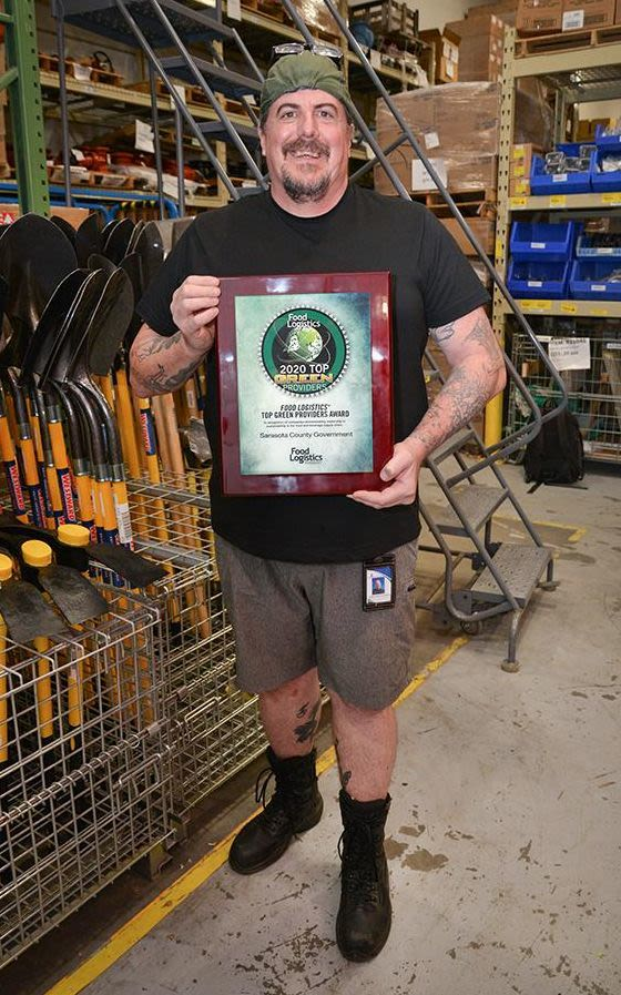 Sarasota County Materials Management team member Ted Monaghan holds the 2020 Top Green Provider Award from Food Logistics.