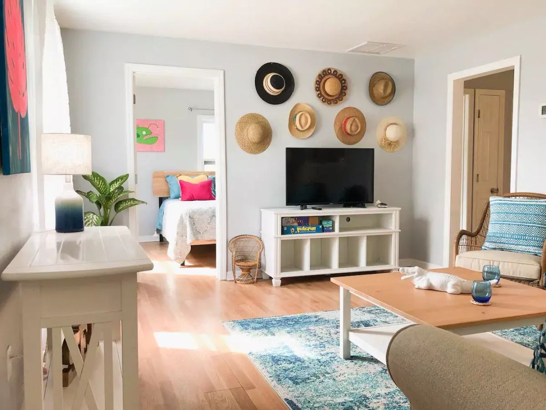 We're charmed by this hat-decorated wall, beachy color scheme and fun art pieces.