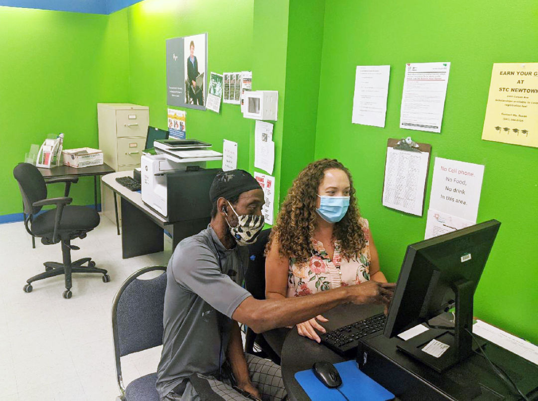 Goodwill mission services program administrator Antonia Quiros assists community member Gregory Morrison at Goodwill's Selby Newtown Job Connection office
