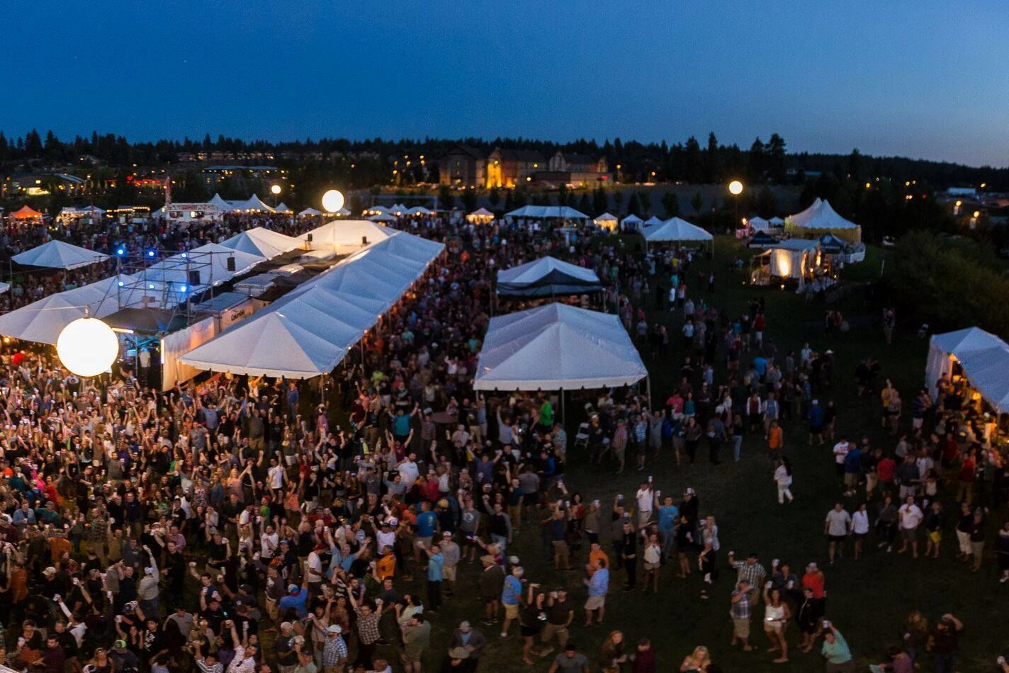 An image during the evening of the bend brewfest in bends old mill district. image courtesy of bend brewfest s8xhqd