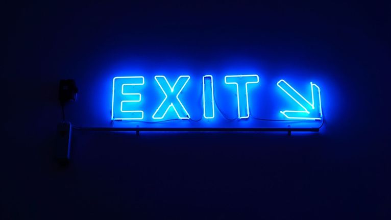 A huge Exit Neon Sign with an arrow beside it