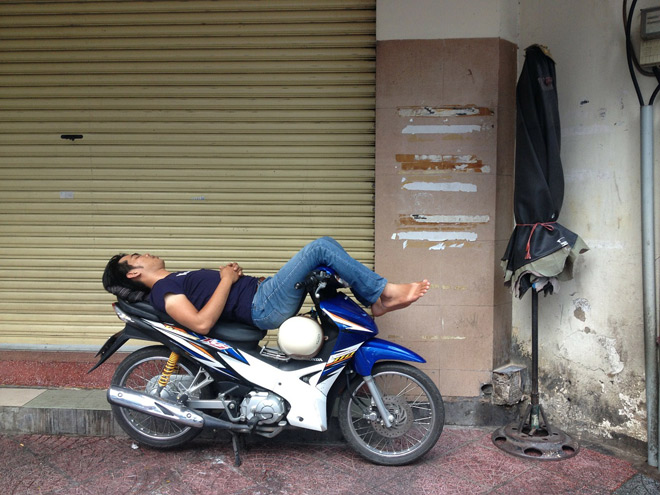 A man sleeps on his moped