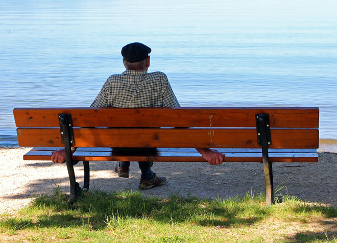 Man Sitting Along on a Bench