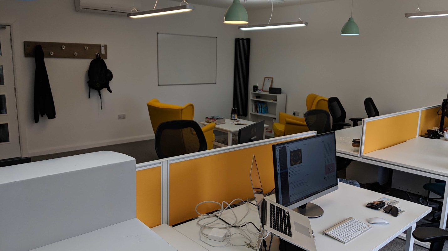The BuddieUp studio showing desks and monitors with yellow accents.