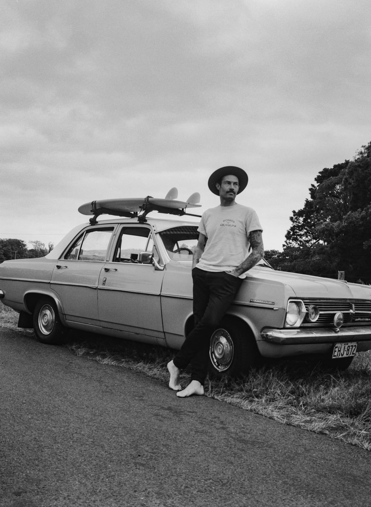 Rob McCann posing with a nice vintage car and a surfboard