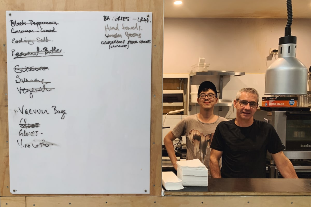 A chef at Sample's kitchen with the updates board