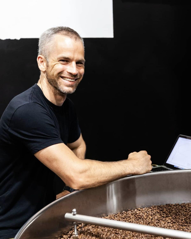 Reuben Mardan posing next to a coffee roaster