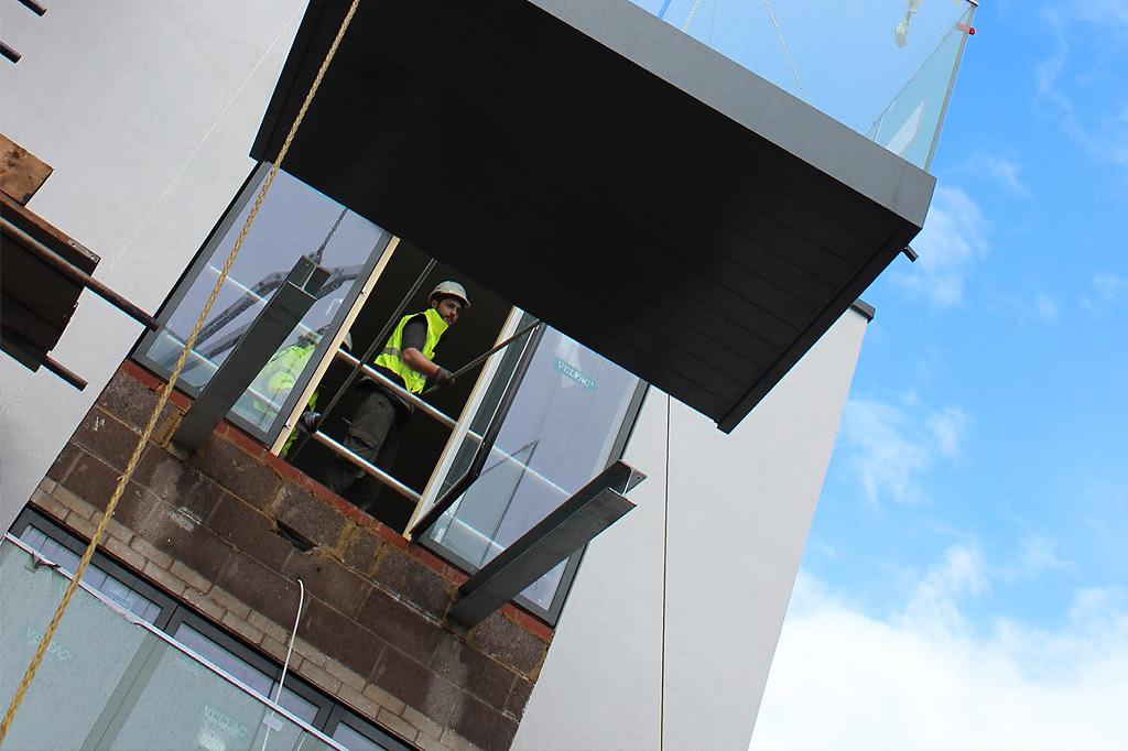 Glide-On balconies on UK construction site. Worker indoors.