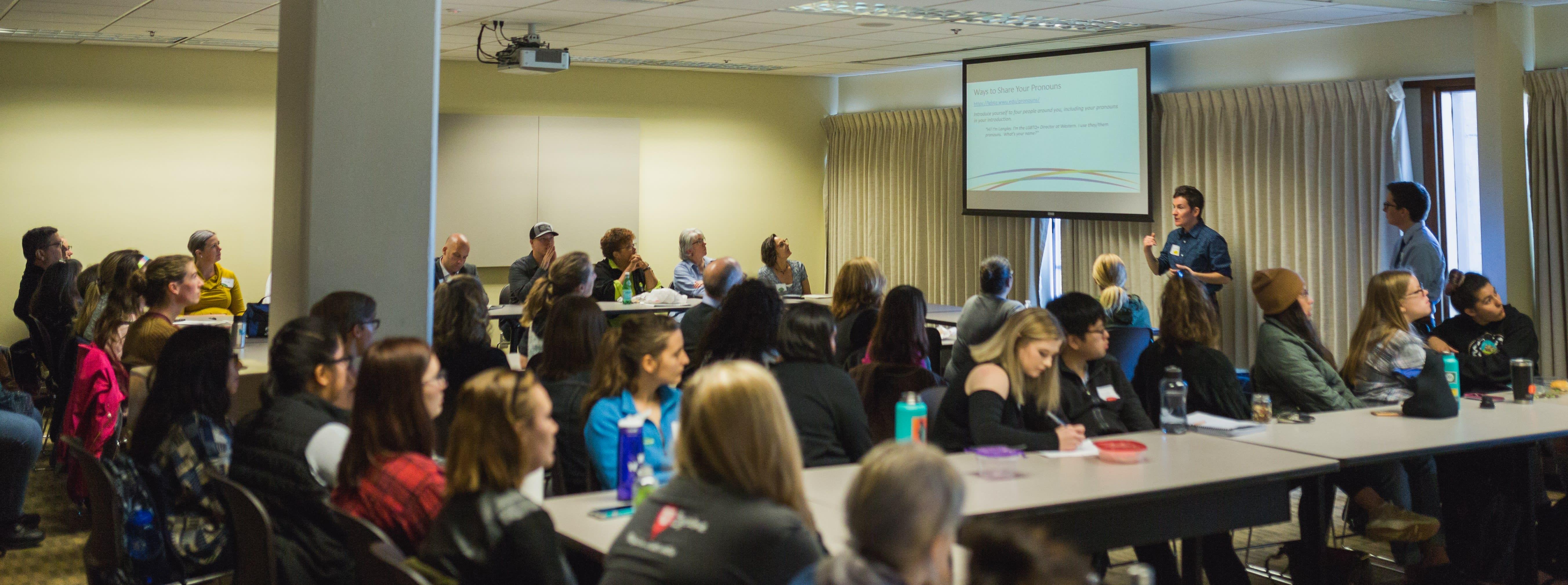 Photo of 2 facilitators leading full room of workshop participants.