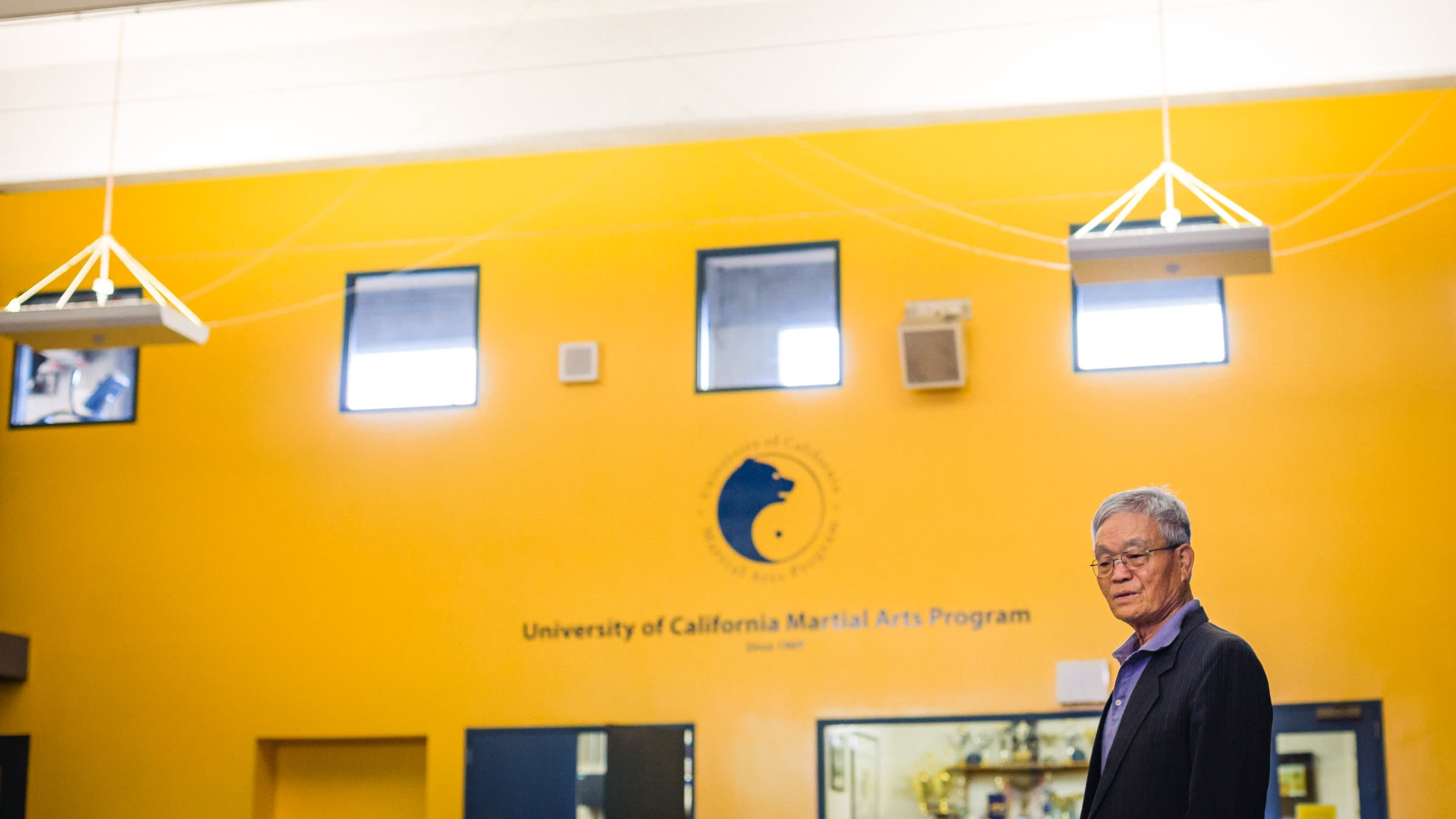 An older Korean gentleman in a suit jacket and button-down shirt against a bright yellow wall. Dr. Min in 2016 in 145 RSF, addressing students.