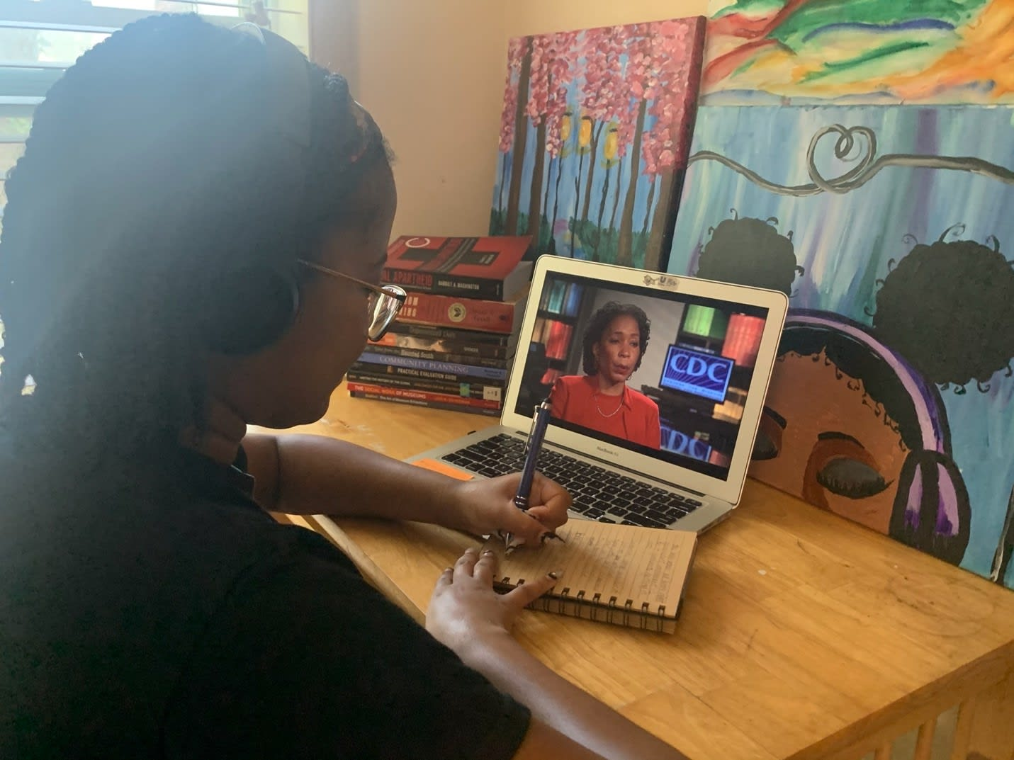 Deniseya Hall sits at a desk with art behind the computer, taking notes on a notebook while watching a presentation on a laptop from the CDC.