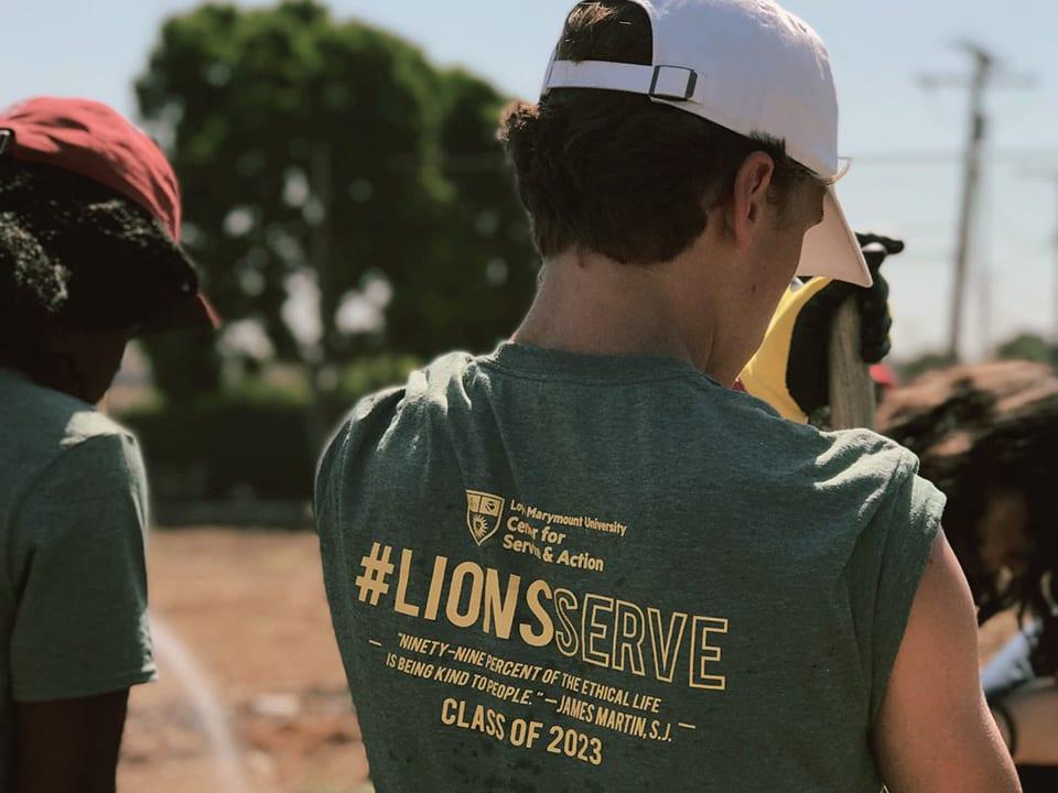 Young man wearing a Lion's serve shirt, back profile