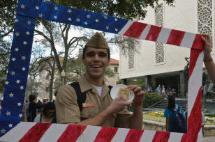 Man dressed in Military clothing posing with a pie