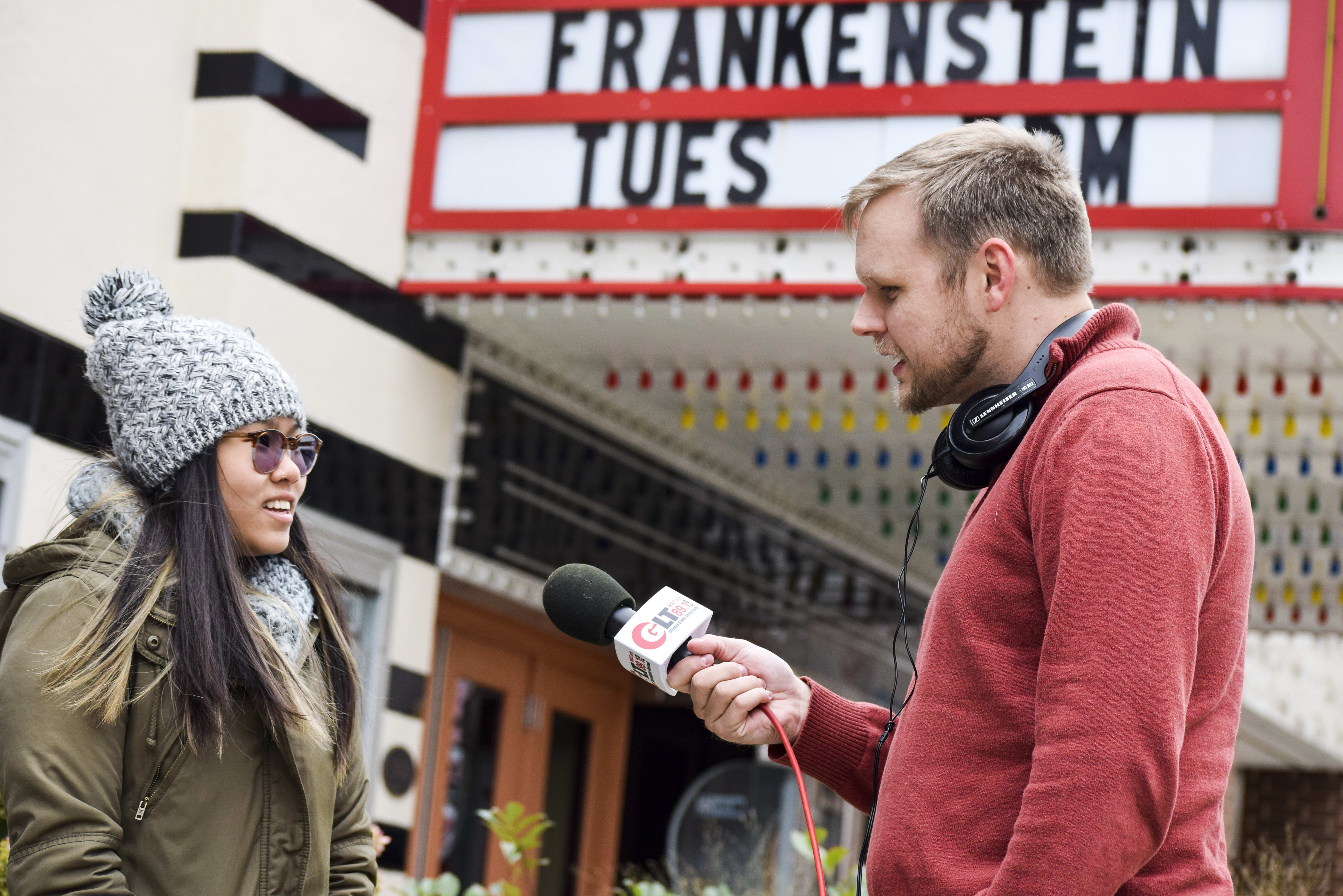 WGLT's Ryan Denham interviewing someone outside the Normal Theatre.