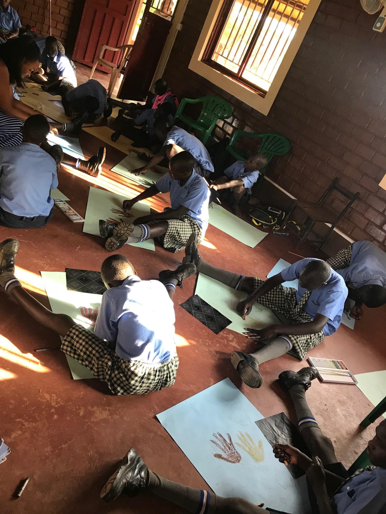 Men sitting on floor drawing