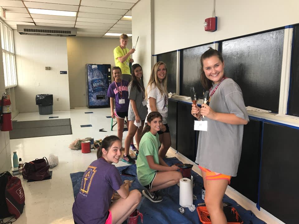 Students painting for a community project