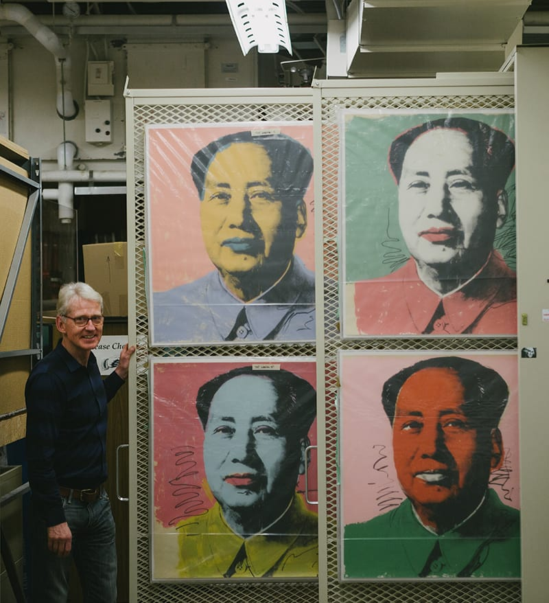 gallery director displays images of Warhol's Chairman Mao