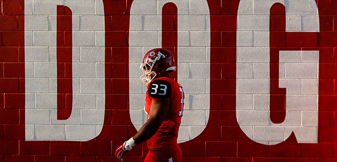 Fresno State Football player walking next to a wall with the words 'DOG' on gameday