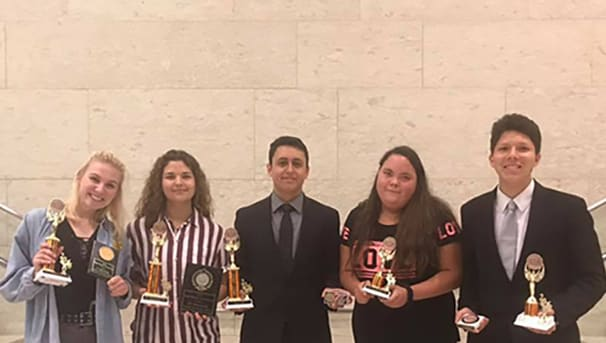 Debate team with trophies