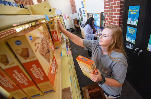 Volunteer putting groceries on shelf