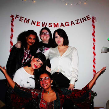 FEM members gathered in front of a red sign that says FEM Newsmagazine