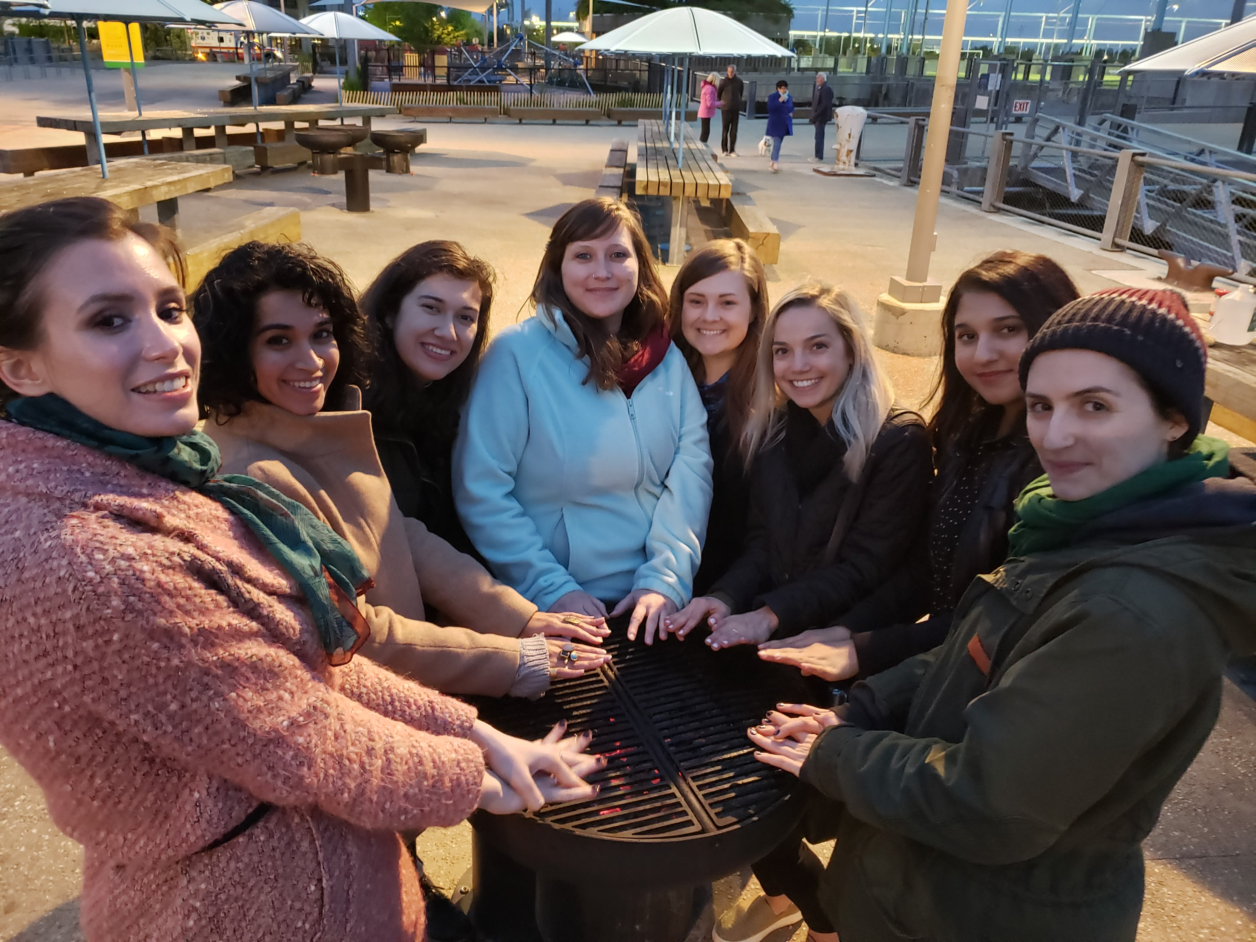 Students posing around fire smiling