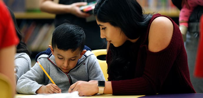 A Fresno State student helps a young child learn how to read.