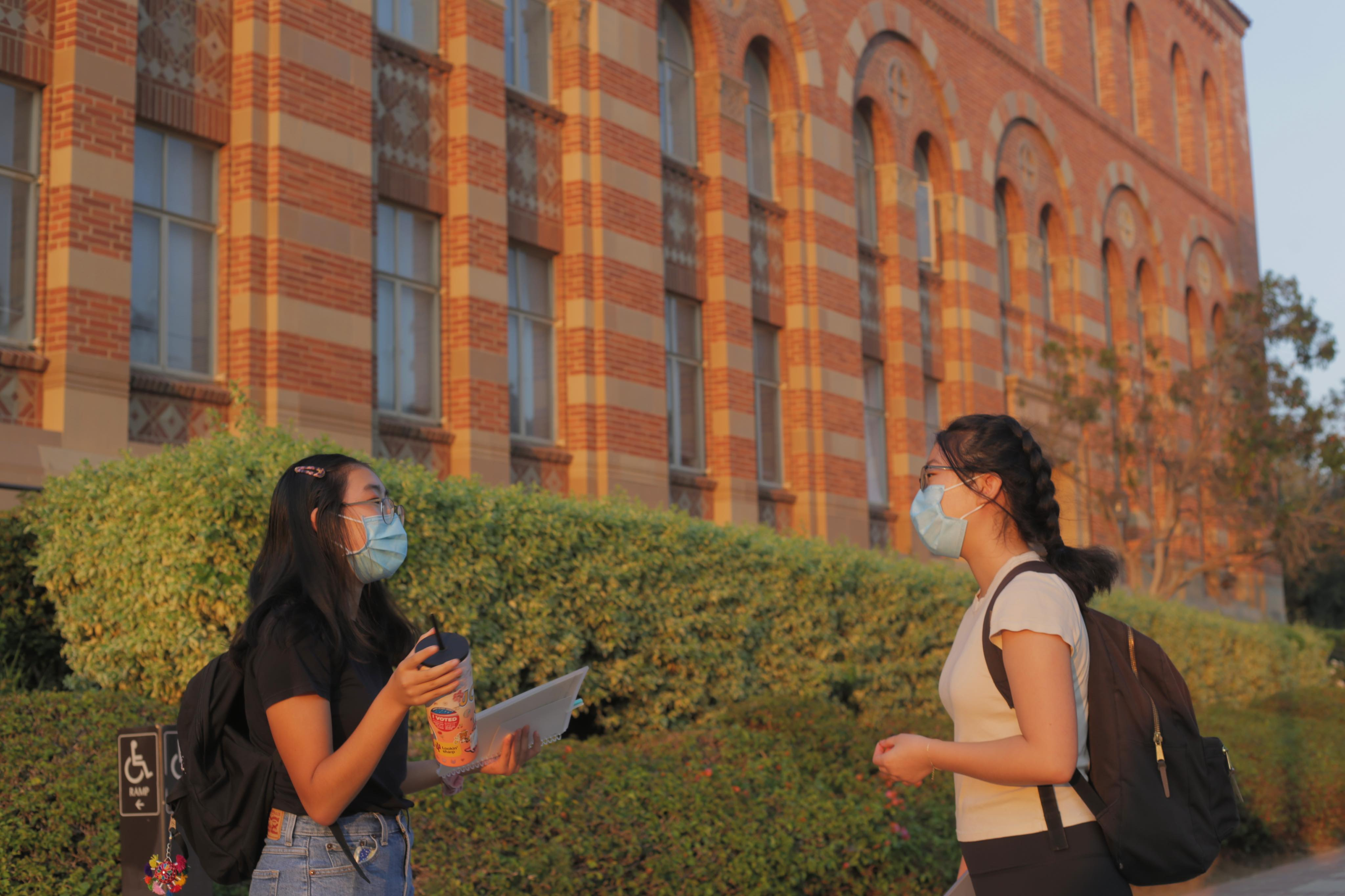 Two students talking in front of Haines Hall.