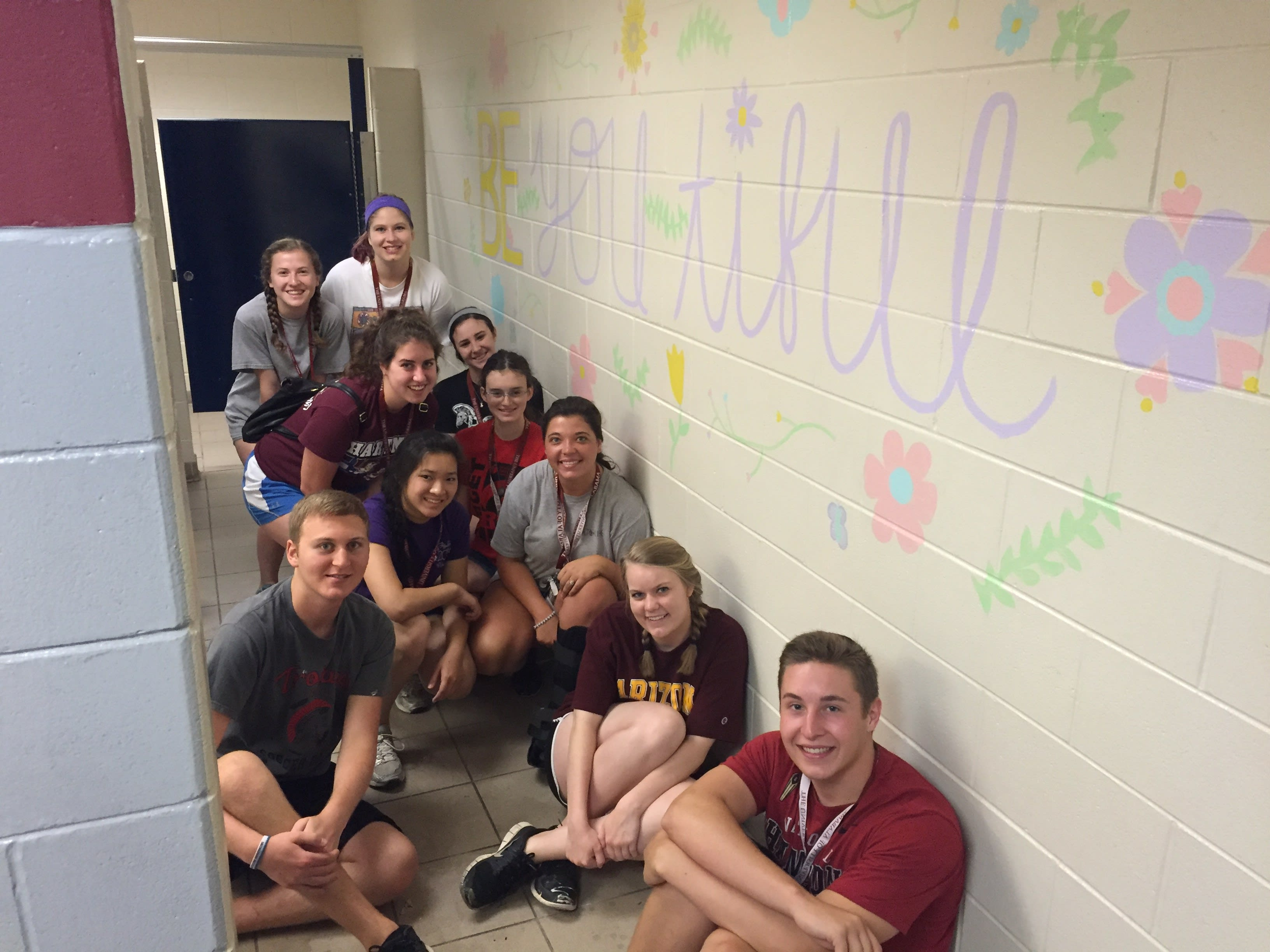 Students painting inspirational message a community project