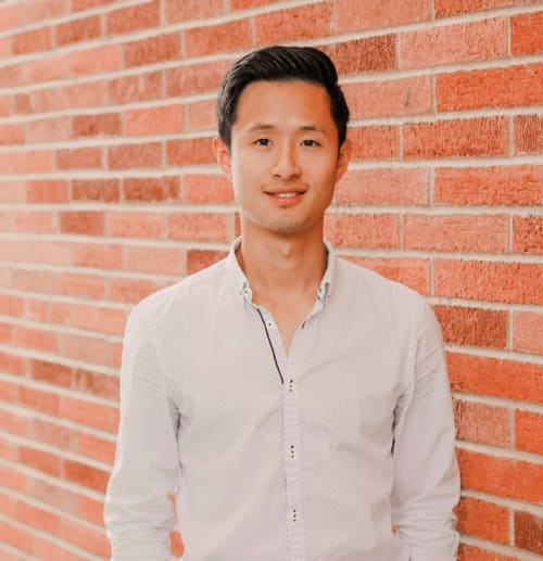 Headshot of Kwang Kim, medical student, against a brick wall