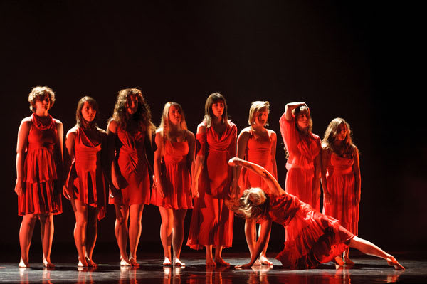 seven dancers in red light, with one dancer propped on the floor at angle in front