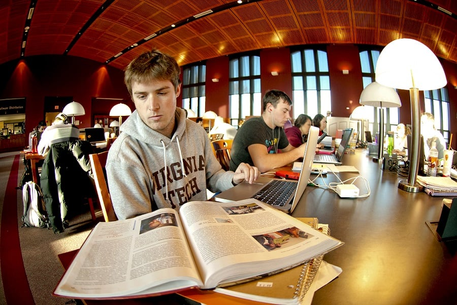 Students studying in Torgerson Bridge at Virginia Tech with books and a computer.