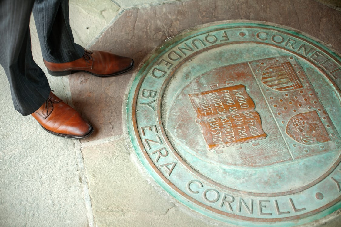 Student in professional attire next to Cornell shield