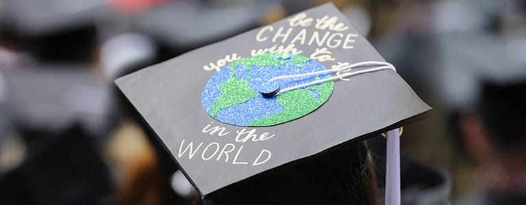 "Graduation cap with ""Be the change you wish to be in the world"" wriiten on it."