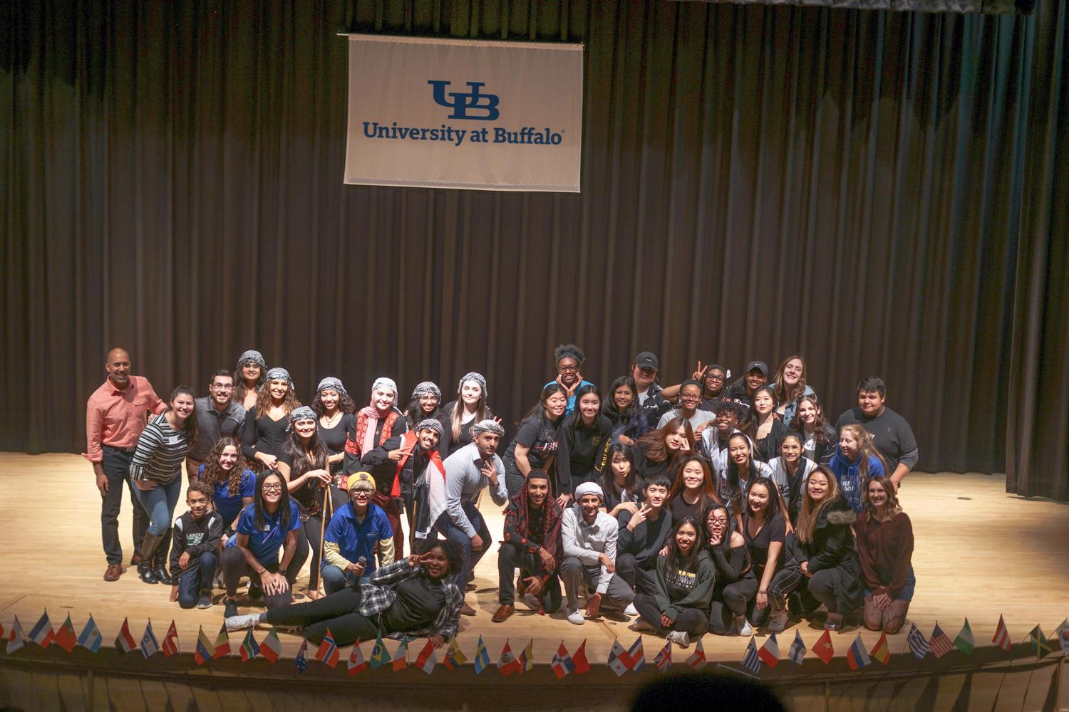 Group Photo of the Residence Hall Association and all of the performers from the November 2019 Cultural Showcase program on the stage in the student union with a banner of the interlocking UB logo.