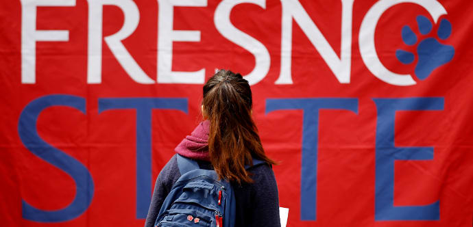 A Fresno State female student gazes at a large banner with the Fresno State logo