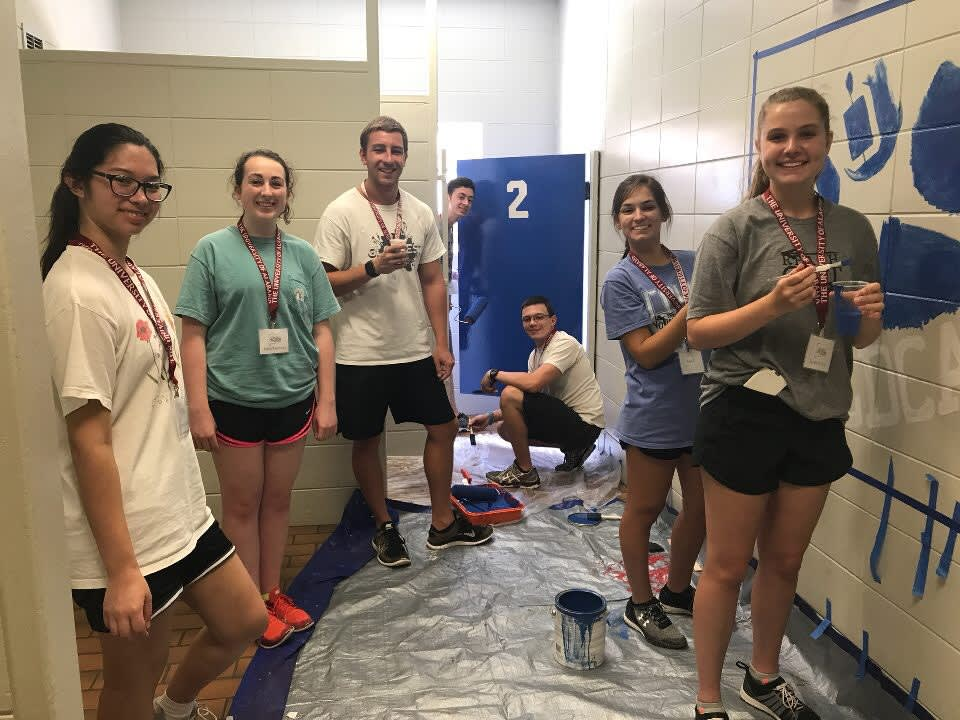 Students painting a restroom for a community project