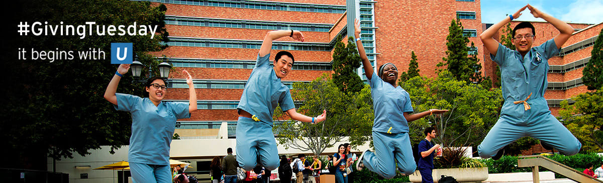 Image of four medical students wearing scrubs jumping up and spelling out U-C-L-A with their bodies.