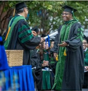 Dr. Festus Ohan recieving his medical school diploma.