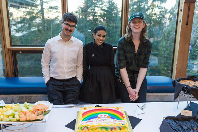 3 students standing behind cake with rainbow