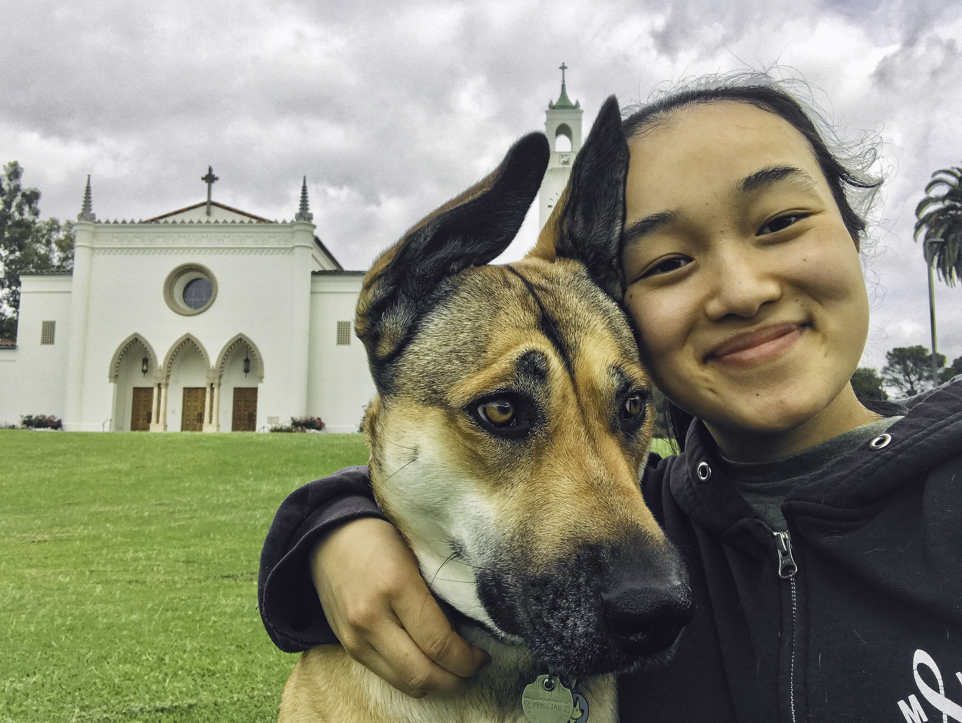 Lucille Njoo and her german shepherd in front of the chapel