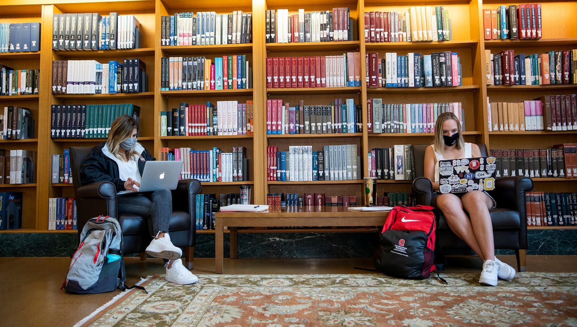 Two students wearing masks studying in library six feet apart