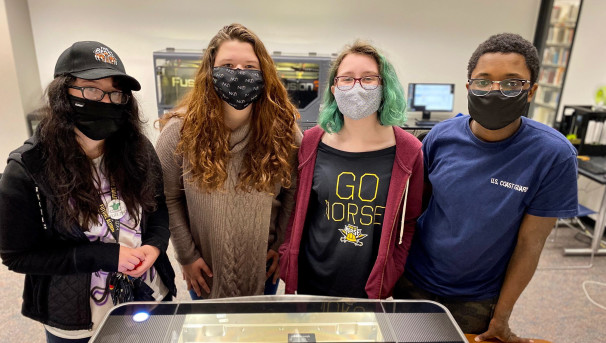 Student makers hovering over Glowforge laser cutter looking at the camera.