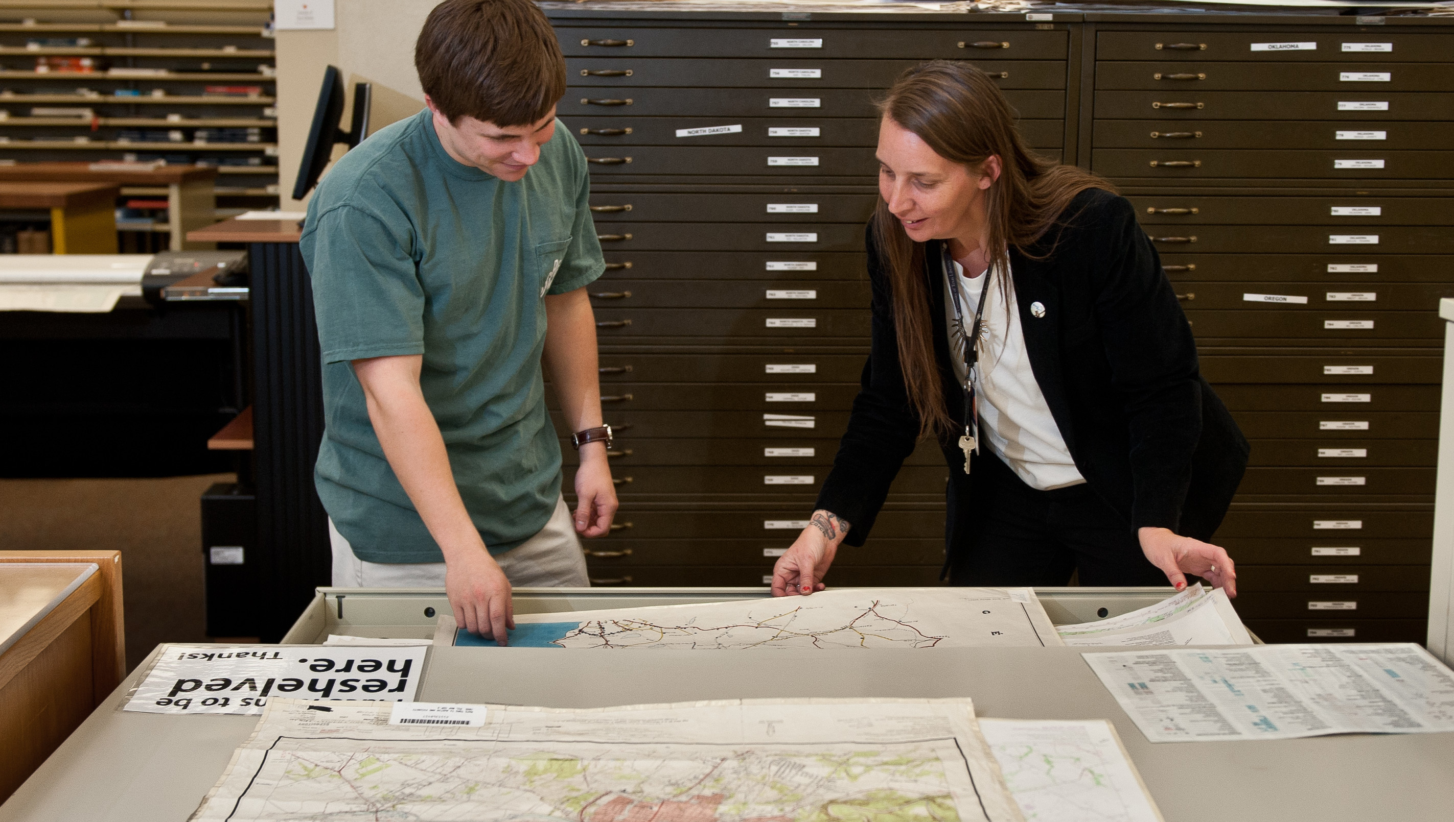 Katherine Strickland, the UT Libraries' Maps Coordinator, helping a student