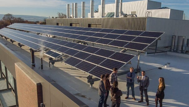 IEM students and professor next to solar panels array atop building roof
