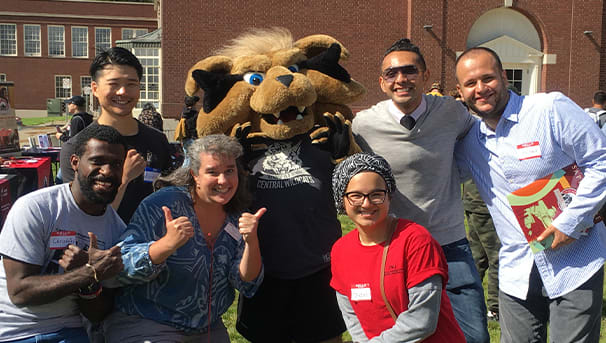 Group of International students and staff posing with Wellington on CWU campus