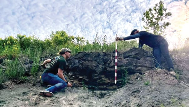 Two OHIO Geological Sciences students working on a rock