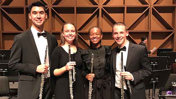 four students with flutes