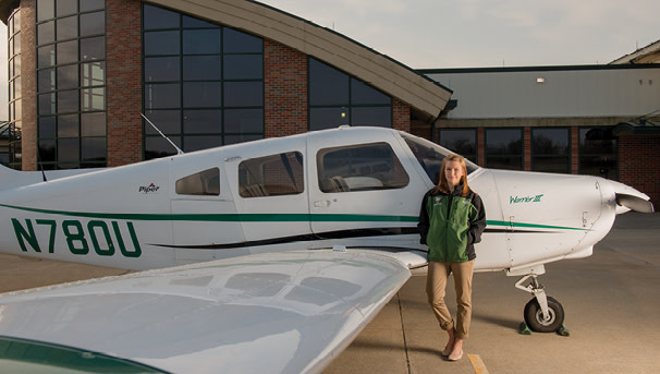 Ohio University student standing next to a plane at OHIO's Airport