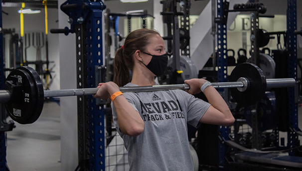 Athlete lifting weights with mask